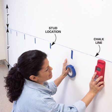<b>Photo 1: Snap level chalk line and locate studs</b></br> Snap a level chalk line to mark the bottom edge of the plywood. Locate studs and mark them with masking tape.
