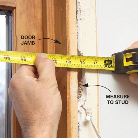 <b>Photo 1: Measure the rough opening</b></br> Pry the interior trim free. Then chip away drywall to expose framing and measure the rough opening width (distance between studs) and height (floor to beam). Then select a new door that fits that rough opening.