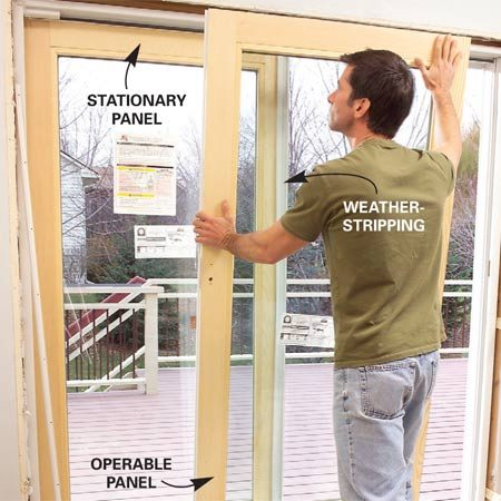 <b>Photo 10: Tip in the glass panels</b></br> Tip the stationary panel into the opening, push it against the door frame and install any angle brackets to anchor it (Photo 3). Tip the operable panel into place and screw the inside head stop to the top of the door frame.