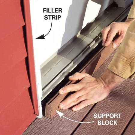 <b>Photo 13: Add filler strips</b></br> Cut filler strips to fit between the door frame and the siding with a 1/8-in. gap on both sides, then fill the gaps with silicone caulk. Cut a threshold support block to fit between the deck and the siding, then slip it into place and nail it.