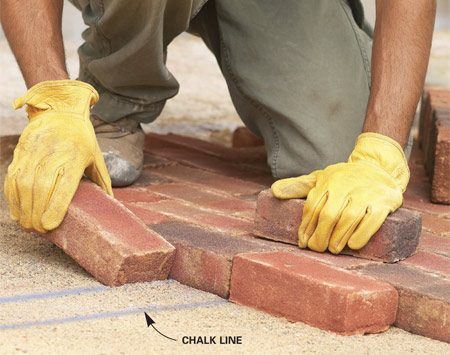 <b>Use a standard chalk line reel</b></br> You can stretch a string between stakes to create a layout line for setting bricks, but simply snapping a chalk line in the sand is quicker, plus you don't have a string in the way. With layout lines snapped on the sand, laying bricks is faster and easier. The chalk won't stick to dry sand, so you may have to mist the sand with water before snapping lines. Then snap layout lines directly on the sand using a standard carpenter's chalk line reel.
