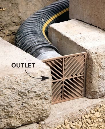 <b>Add outlets at 16-ft. intervals</b></br> Then add outlets at about 16-ft. intervals. Cover the tubing with crushed stone. Then continue filling behind the wall with crushed stone as you build it.
