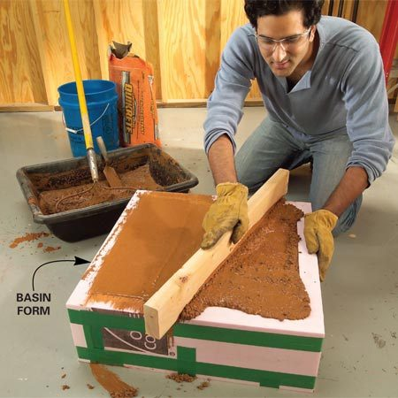 """<b>Photo 6: Level concrete in the basin form</b></br> Fill the basin form and """"screed"""" off the excess concrete with a 2x4. Let the concrete cure for a week before you remove any of the forms."""
