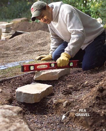 <b>Photo 2:  Lay the first stones</b></br> Set stones on the gravel and check for level. Add or remove gravel to form a level base all along the trench.