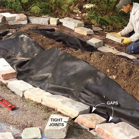 <b>Photo 4: Start the second course</b></br> Add a second course of stones, mixing sizes and staggering the joints from the base course. Keep the joints tight on the exposed side.