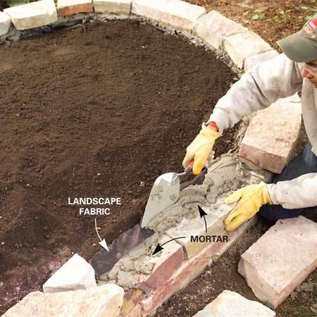 <b>Photo 9: Mortar the capstones in place</b></br> Remove a few capstones at a time and lay a 1/2-in.-thick bed of mortar over the back half of the wall. Fold the fabric over the mortar. Add another 1/2 in. of mortar, then set the capstones in place.