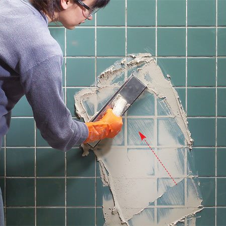 <b>Photo 5: Pack the joints</b></br> Spread grout at an angle to the grout lines with a rubber float. Press hard on the float to pack the joints full of grout.