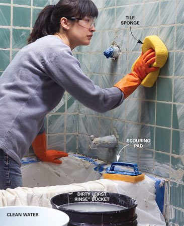 "<b>Photo 7: Clean with sponge</b></br> Wipe off the excess grout with a damp sponge as soon as the grout lines are firm. To keep the rinse water clean, dip the sponge in the ""dirty"" bucket and wring it out. Then dip it in the ""clean"" bucket and wring it over the dirty bucket."
