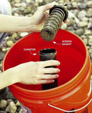 <b>Photo 1: Unscrew the top</b></br> Disassemble the sprinkler head by unscrewing the top from the canister. Rinse away soil and debris in a bucket of water.