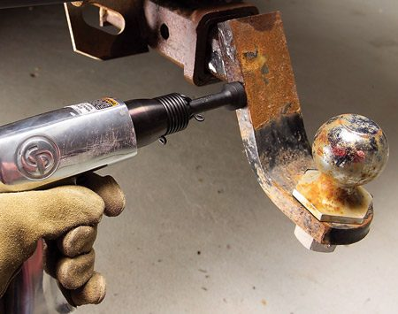 <b>Photo 2: Rap with an air hammer</b></br> Rap the sides, top and bottom of the hitch receiver for 15 seconds with blows from the air hammer. Spray again. Repeat the rapping until the ball mount loosens.
