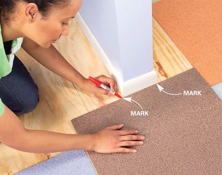 <b>Photo 6: Mark cuts in place</b></br> Place a carpet square right side up against an archway wall, aligning it with installed squares. Mark the wall location on the edges of the carpet.