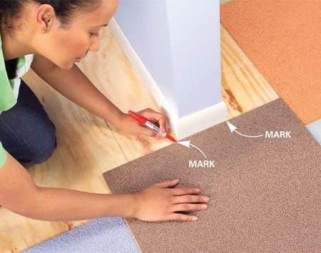 <b>Photo 6: Mark cuts in place</b><br/>Place a carpet square right side up against an archway wall, aligning it with installed squares. Mark the wall location on the edges of the carpet.