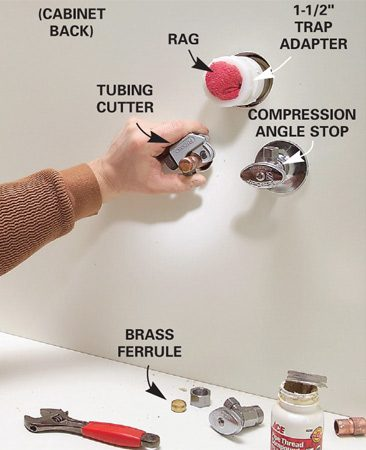 <b>Photo 7: Install the angle stop valves</b></br> Fit the sink base over the stubouts. Then cut the copper pipes about 2 in. beyond the cabinet back and install the angle stop valves. Cut back the PVC drainpipe and glue on a 1-1/2-in. trap adapter.