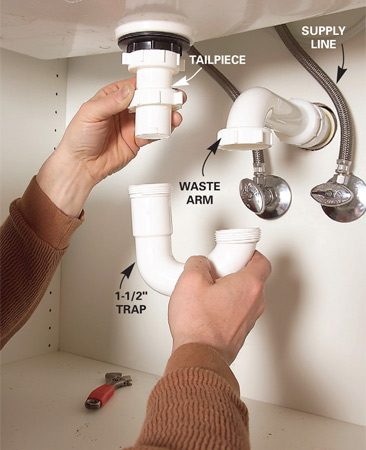 <b>Photo 9: Attach the trap and supply lines</b></br> Connect the sink to the drain with a plastic trap assembly. Hand-tighten the slip-joint nuts. Then tighten them an additional quarter turn with large slip-joint pliers. Connect the supply lines.