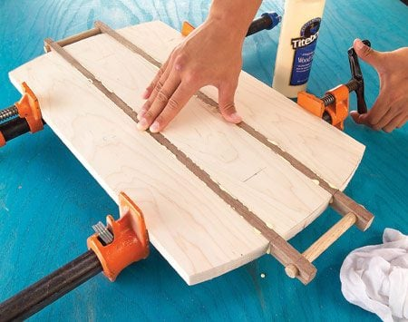 <b>Photo 2: Assemble</b></br> Take the boards out of the clamp, saw and sand the arcs on each board, and then glue the assembly together, leaving the dowel handles unglued.