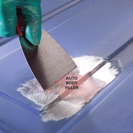 <b>Photo 2: Apply auto body filler</b></br> Mix auto body filler and fill the dent using a wide putty knife. Avoid leaving humps or ridges. If necessary, add more filler after the first layer hardens.