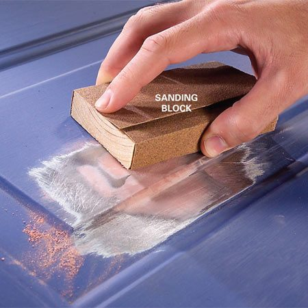 <b>Photo 3: Sand the filler smooth </b></br> Sand the filler smooth with 100-grit paper. Use a sanding block to ensure a flat surface. Prime the repair and paint the entire door.