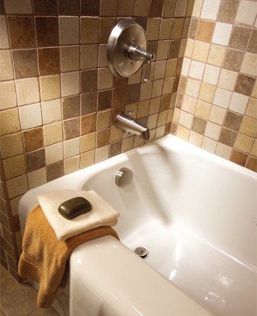 "<b>Photo 2: New faucet and a refinished tub</b></br> The brushed nickel finish was selected for its long wear and because ""it simply doesn't show dirt as much,"" says designer Matthew Rain. The bathtub was refinished so it would match the clean white color of the new fixtures."