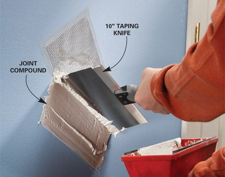 <b>Photo 2: Cover with drywall compound</b></br> Spread the first coat of joint compound over the patch with a wide taping knife. Let it dry overnight.
