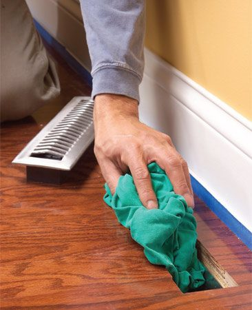 <b>Photo 2: Prep the room</b></br> Plug heating ducts with old towels, close windows and turn off fans to limit dust. Protect baseboards with painter's tape.