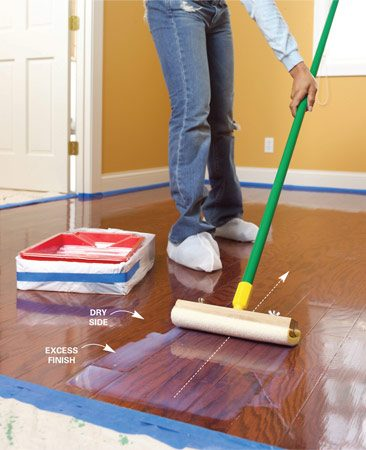 <b>Photo 10: Spread the finish</b></br> Gently plow the finish with the grain of the wood. Pull the applicator at an angle so the excess finish puddles on the dry side of the floor.