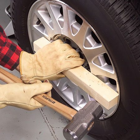 <b>Photo 2: Knock the wheel free</b></br> Place the wood near the edge of the wheel and give it a good smack. Rotate the tire a quarter turn and hit it again. Repeat until the wheel breaks free.
