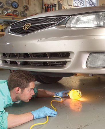 <b>Photo 2: Check for fluid leaks</b></br> Small leaks often turn into gushers once you leave town, and that can be costly. The most common sources: the radiator, engine oil pan, transmission oil pan and hoses, power steering hoses, steering rack, and heater and radiator hoses. Use a flashlight to check for leaks. Note the color of the fluid and trace the fluid trails back to their source.