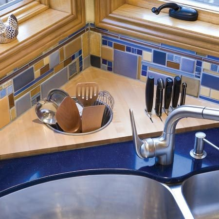 <b>Corner space</b></br> The corner counter space behind the sink was put to good use with this customized butcherblock top. The knife storage area is enclosed below the countertop to prevent accidents. A utensil storage bin was recessed into the butcher block and can hold either pot scrubbers or often-used cooking utensils.