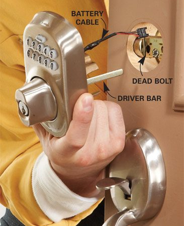 <b>Photo 1: Mount the keypad</b></br> Hold the keypad upright and slide the battery cable over the top of the dead bolt and the driver bar through the center slot of the dead bolt.