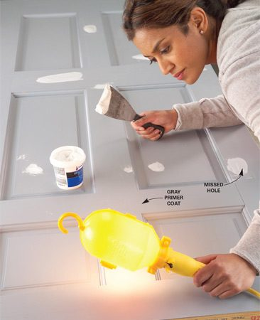 <b>Check for flaws</b></br> Shine a light at a low angle across the door after priming to locate any missed scratches, dents or pinholes.
