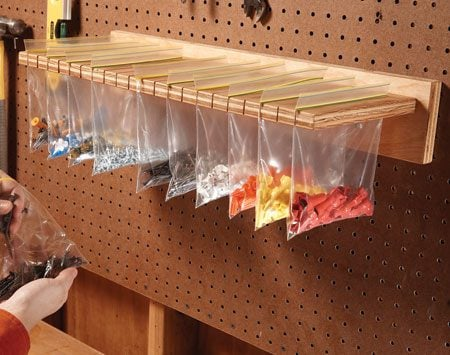 <b>Small parts storage</b></br> Cut slots in a piece of plywood with a jigsaw. Fill resealable bags with small parts, hardware or craft items and hang them from the slotted plywood.