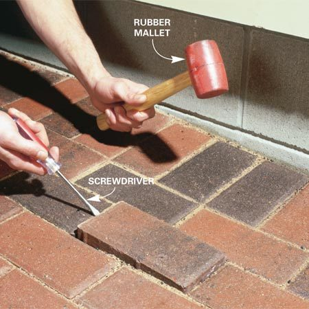 <b>Photo 1: Remove the pavers</b></br> Pry up the paver with a thin screwdriver, pounding on adjoined pavers to vibrate packed sand loose.