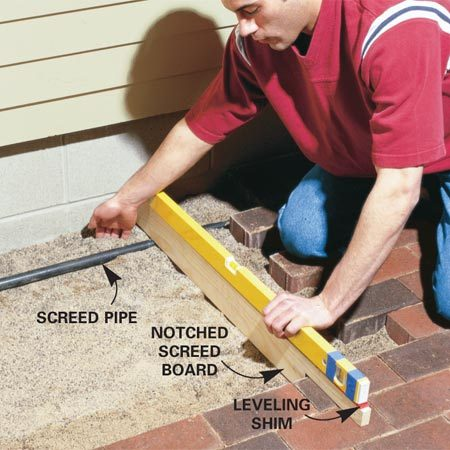 <b>Photo 2: Level the screed pipe</b></br> Level a screed pipe using a screed board with a notch at one end 1/8 in. shallower than the depth of the pavers.