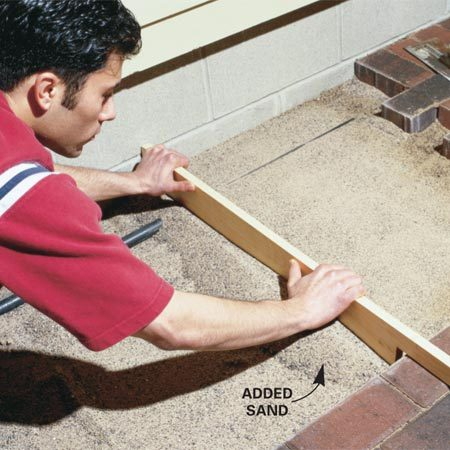 <b>Photo 3: Add and screed the sand</b></br> Add sand to the low area, then level it by pulling the screed board along the pipe and the pavers.
