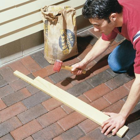 <b>Photo 4: Tap down the pavers</b></br> Remove the screed pipe and set the pavers back, tapping them down level with a board.