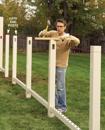 <b>Photo 6: Align posts</b><br/>Stretch the string even with the top of the rail holes on the end posts. Drive each line post down to align the rail holes.