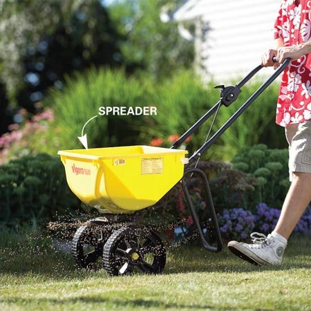 <b>Photo 2: Application</b></br> Apply crabgrass preemergence granules with a spreader, especially around driveways and walks and also alongside the neighbor's crabgrass-infested yard.