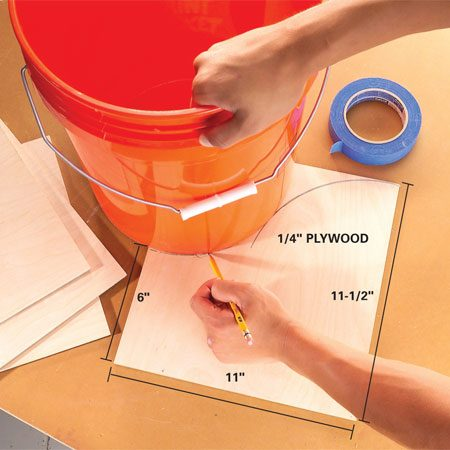 <b>Photo 1: Mark the cuts</b></br> Cut the 1/4-in. plywood into eight 11-1/2-in. x 11-in. pieces. Use a 5-gallon bucket to trace a graceful S-curve from the 11-1/2-in.-high corner across the plywood to a 6-in. mark on the opposite side. Simply establish a smooth curve.