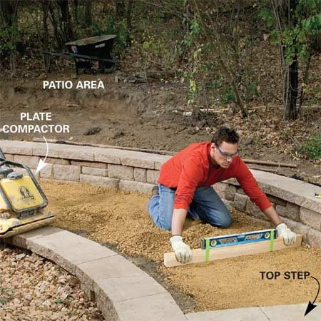 <b>Photo 10: Roughly level the path</b></br> Dig out the path area 9 in. below the top step, lay woven fabric and fill with two 3-in. layers of gravel, tamping between layers with a plate compactor. Roughly level the second layer before compacting.