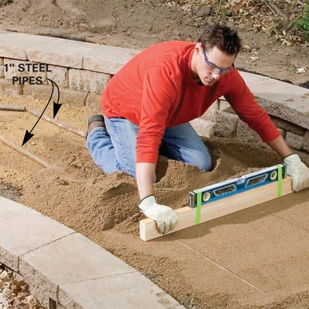 <b>Photo 11: Screed the path</b></br> Dump a 1-in. layer of sand over the gravel and screed it smooth using 1-in. steel pipes as guides. Remove the pipes and fill the pipe grooves with sand. Smooth the edges with a trowel.