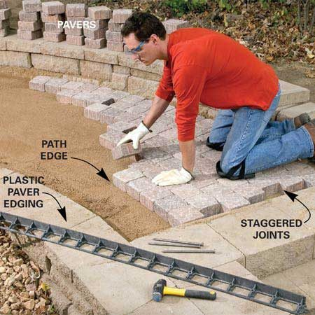 <b>Photo 12: Set the pavers</b></br> Drop in the pavers, staggering the joints. Begin at one end and work from the retaining wall side to the open side. Nail the plastic edging to the gravel. Tamp pavers with the plate compactor.