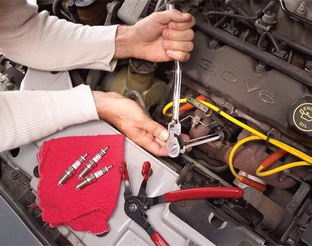 <b>Photo 3: Unscrew the plug</b></br> Blow debris away from the spark plug recess before removing the spark plug. Using the swivel spark plug socket and an extension, unscrew the spark plug.