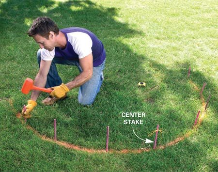 <b>Photo 3: Drive stakes in the arc</b></br> Space nine stakes evenly around the semicircle, and drive them down about 5 in. Mark the middle stake with a string.