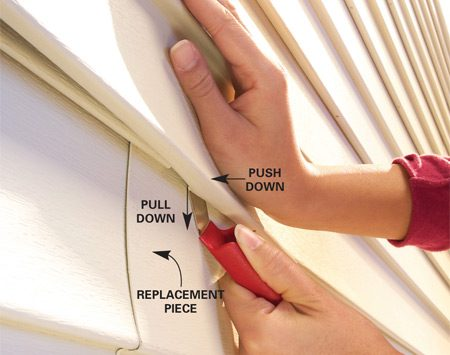 <b>Photo 3: Install new siding</b></br> Install the replacement piece and hook the lip of the upper siding piece into the slot to lock it into place.