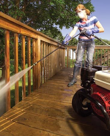 <b>Photo 1: Clean the railings</b></br> Pressure-wash the railings with stripper. Keep the tip 6 to 10 in. from the wood and work from the top down. Spray balusters at the corners to scour two sides at once.
