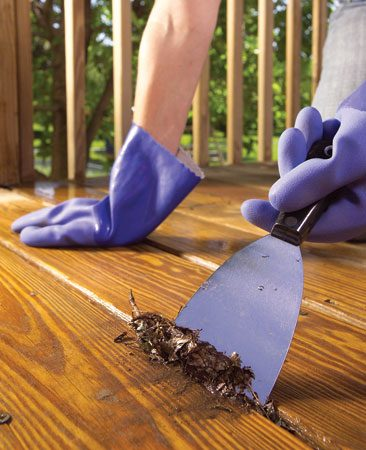 <b>Photo 3: Clean out the gaps between decking </b></br> Dig out trapped debris from between deck boards with a putty knife. Spray the deck lightly with a mixture of oxalic acid and water to brighten the wood.