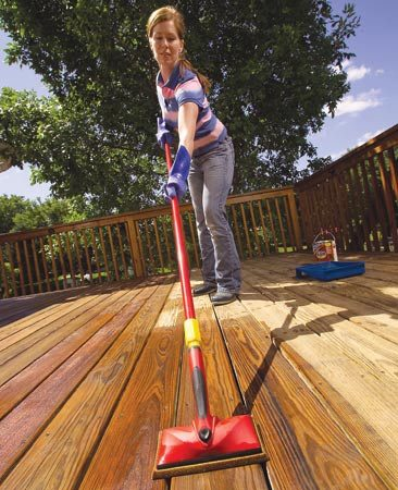 <b>Photo 9: Use an extension pole on the decking</b></br> Stain the deck boards using a foam applicator pad with an extension handle. Stain the full length of two or three boards at a time, working with the grain.