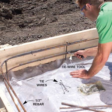 <b>Photo 5: Tie in the rebar</b></br> Cover the fill with a layer of 6-mil plastic sheeting. Tie two bands of 1/2-in. steel reinforcing rods (rebar) to stakes set about 4 in. from the perimeter of the forms (Figure A).