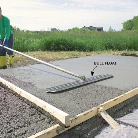<b>Photo 8: Flatten with a bull float</b></br> Push a bull float across the screeded concrete, keeping the leading edge slightly elevated. When you reach the far side, lift the handle enough to slightly elevate the edge closest to you and pull back to the starting point. Move over and repeat, overlapping the previously floated surface by about one-third.