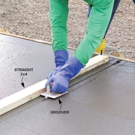 <b>Photo 11: Cut control joints</b></br> Form control joints to minimize random cracks by running a groover along the edge of a straight 2x4. Work the groover forward and back while making a progressively deeper cut.